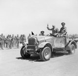 Winston Churchill giving his famous V-for-Victory sign while being driven past a line of troops in Tel-el-Kebir, 9 August 1942.