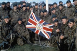 Naval Party 8901, the Royal Marine garrison of the Falkland Islands evicted by the Argentine invaders, with the Falkland Islands flag outside Government House, Port Stanley, after the Argentine surrender, June 1982.