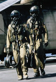 Crew from a Westland Sea King HC.4  of 'A' Flight, 846 Naval Air Squadron walking away from their helicopter wearing NBC [Nuclear Biological and Chemical] suits during the Gulf War, 1991