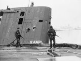 Royal Marines patrol past the abandoned Argentine submarine SANTA FE on South Georgia, 28 May 1982.