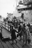 A Dutch school teacher leads a group of refugee children just disembarked from a ship at Tilbury Docks in Essex during 1945.