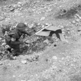 An RAMC medical orderly makes his way forward under cover of the Red Cross flag to recover a casualty during fighting at Cassino, 24 March 1944.