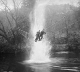 Commandos cross a river on a 'toggle bridge' under simulated artillery fire at the Commando training depot at Achnacarry in Scotland, January 1943.