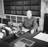 Winston Churchill makes a radio address from his desk at 10 Downing Street, wearing his 'siren suit', June 1942.