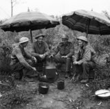 Gunners of 78th Field Regiment, Royal Artillery make use of 'liberated' sunshades to keep the rain off while making a brew, Anzio, Italy, 27 February 1944.
