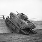 A Churchill tank of 79th Armoured Division uses a Churchill Ark to scale a sea wall during trials near Saxmundham, 11 March 1944.