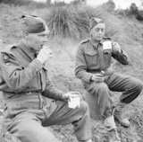 Soldiers from the 78th Division enjoying tea and cakes served by a Salvation Army van in the forward area, Italy, 28 November 1943.