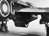 A practice 'Upkeep' weapon attached to the bomb bay of Wing Commander Guy Gibson's Avro Lancaster of No. 617 Squadron at Manston, while conducting dropping trials for the Dams Raid off Reculver, May 1943.