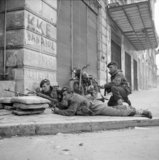 Paras from 5th (Scots) Parachute Battalion, 2nd Parachute Brigade, take cover on a street corner in Athens during operations against members of ELAS, 6 December 1944.