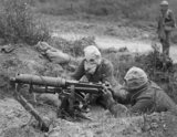 A Vickers machine gun team wearing PH Type anti-gas helmets in action near Ovillers during the Battle of the Somme, 1916.