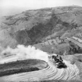 A Priest 105mm self-propelled gun negotiates a hairpin bend on a mountain road near Mondaino during the advance through the Gothic Line, Italy, 6 September 1944.