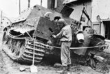 A US soldier examines a knocked-out Sturmtiger assault gun, Germany 1945.