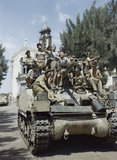 Local children crowd aboard a Sherman Mk III tank of the County of London Yeomanry in the village of Milo near Catania in Sicily, August 1943.