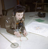 A member of the Auxiliary Territorial Service, Miss Elizabeth Amery, computes the range at 428 Battery, Coastal Defence Artillery Headquarters, Dover, December 1942.