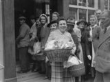 Mrs Bell from Guernsey shows off the contents of her full shopping baskets after the liberation of the Channel Islands in 1945.