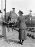 A female railway worker employed during the First World War prepares to operate points for an oncoming train, 1918.
