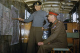 King George VI listens as Field Marshal Sir Bernard Montgomery outlines his future strategy at his mobile headquarters in Holland, 13 October 1944.