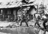 A British infantry patrol cautiously approaches a damaged building in a Burmese village, 1944.