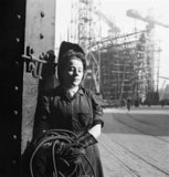 A study of a young woman welder . She is posing for the photographer, leaning against a column. In the background a ship under construction can be seen in a slipway.