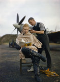 A pilot at Fairlop airfield in Essex has a haircut during a break between sweeps. A Supermarine Spitfire is in the background.