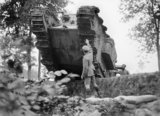 A British soldier directs a Mark IV tank as it crosses an old trench in Oosthoek Wood, near Elverdinghe.