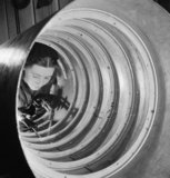 A woman metal worker sweating stiffening rings in a Torpedo Balance Chamber using a gas blow torch.