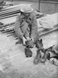 An evacuated soldier, wearing a French overcoat, changes his socks and boots at Dover, 31 May 1940.