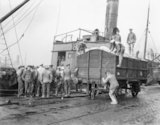 British troops unloading flour from ships and loading into railway trucks. Calais, March 1917.