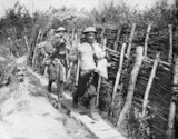 Two Irish Guardsmen going up a communication trench with supplies. Elverdinghe, 30 July 1917.