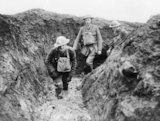 Officers of 12th Royal Irish Rifles wading through mud in a trench, Essigny, 7 February 1918.