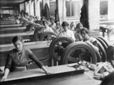A row of women stand at benches to build up the rubber tread on tyres, Lancashire.
