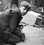 A dishevelled young caulker seals joints on a new ship, Tyneside, 1943
