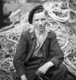 A young shipyard apprentice fitter posed on a pile of steel cables, Tyneside, 1943