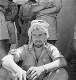 A soldier of the Long Range Desert Group uses a Libyan  keffiyeh scarf to protect his head from the sun, Siwa, Libya, 1942