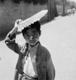 China 1944: A small boy posing with his fan above his head in Chengtu.