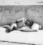 A young naval recruit rests by the harbour wall after reporting for duty at Castle Barracks, Royal Indian Navy Depot, Bombay, India, 1944