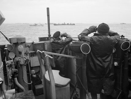 Officers on the bridge of a destroyer, escorting a large convoy of ships keep a sharp look out for attacking enemy submarines during the Battle of the Atlantic, October 1941.