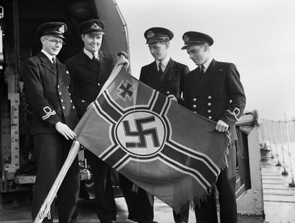 Royal Navy officers aboard the destroyer HMS GARTH with a captured German E-boat ensign at Sheerness, 21 October 1944.