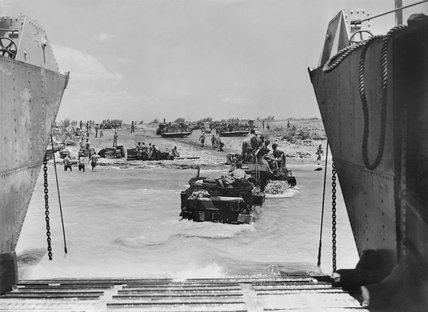 A Universal Carrier is towed to the beach by a bulldozer during the Allied invasion of Sicily, 10 July 1943.