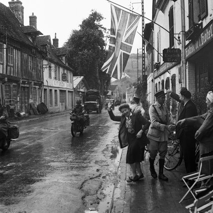 A union flag hangs in the main street of Les Andelys in Normandy as British forces arrive, 31 August 1944. The woman in the foreground is Madame Scarlett, wife of an expatriate Englishman and owner of the Hotel des Fleurs.