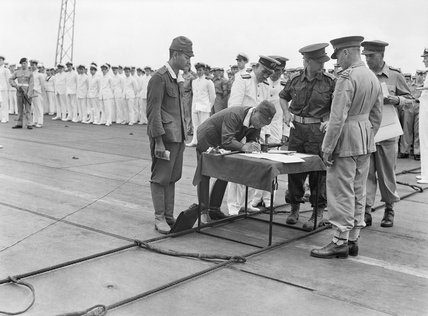 General Imamura signing the official document of surrender for Japanese forces in New Britain, New Ireland, the Solomons and New Guinea, on the flight deck of HMS GLORY off Rabaul, 12 September 1945.