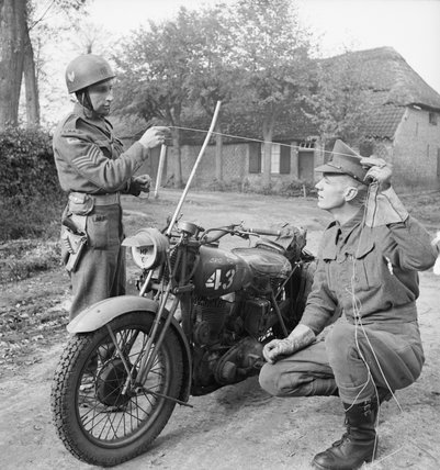 Military Police motorcyclists demonstrate how a metal rod fitted to a motorcycle can prevent the rider from being killed by a wire stretched across the road, 25 October 1944.