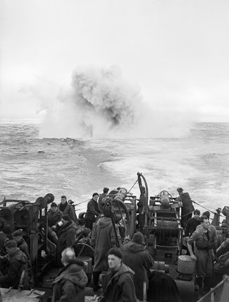Depth charges explode astern of HMS STARLING of the 2nd Escort Group in the Atlantic, January 1944.