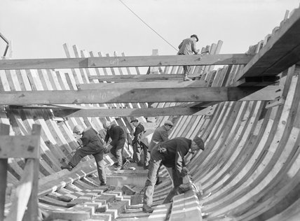 The hull of a minesweeping trawler being constructed using traditional techniques in a shipyard on the east coast of Britain, October 1942.