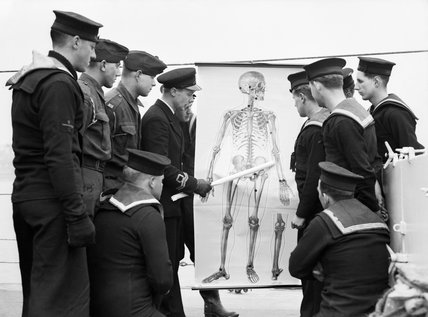 The ship's doctor giving a lecture on first aid to crew members on HMS ATHERSTONE at Plymouth, 7 March 1942.