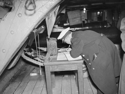 Captain Aden Badhan, Senior Officer of a Peruvian combined services mission to Portsmouth, signing the visitor's book aboard HMS VICTORY, October 1945.