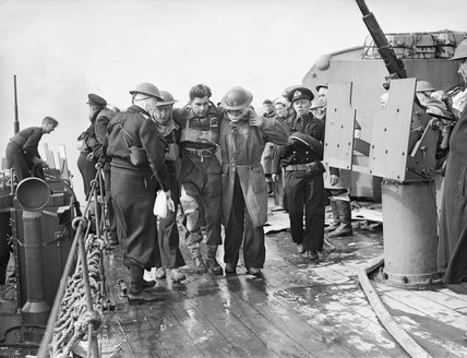 A wounded soldier being helped aboard the cruiser HMS FROBISHER off the Normandy coast, 6 June 1944.