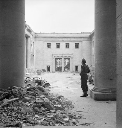 Sergeant R S Baker of the Army Film and Photograph Unit standing in the courtyard of the ruined Chancellery building in Berlin, 2 July 1945.