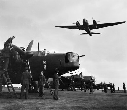 Ground crews of No 300 (Polish) Squadron RAF work on their Vickers Wellington Mk Xs at Hemswell in Lincolnshire, as another aircraft makes a low pass over the flight line, 17 June 1943.