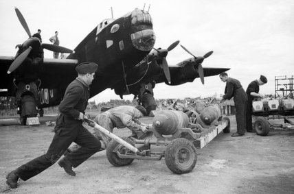 Armourers 'bombing up' a Handley Page Halifax Mk II of No. 405 Squadron RCAF at Pocklington in Yorkshire, August 1942.